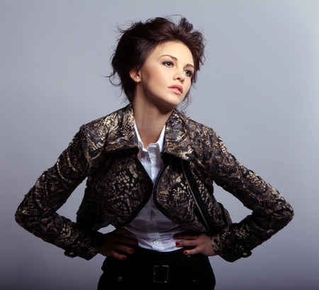 Attractive woman in leather jacket on gray background photo