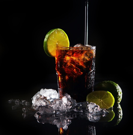 soft drink: Fresh cola drink with ice and green lime on black background Stock Photo