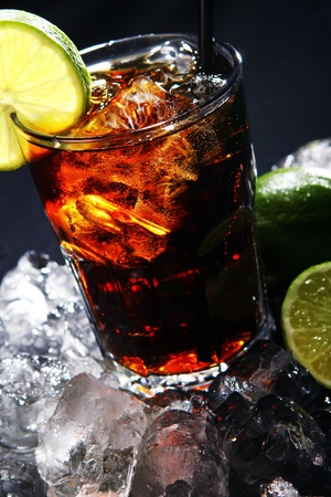 cola: Fresh cola drink with ice and green lime on black background Stock Photo