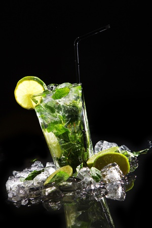 carbonated drink: Fresh drink with splashesh of water, green mint and lime on black background Stock Photo