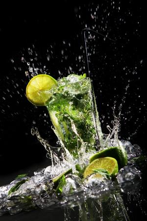 cocteles de frutas: Bebida fresca con splashesh de agua, menta verde y cal sobre fondo negro