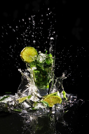 Fresh drink with splashesh of water, green mint and lime on black background photo