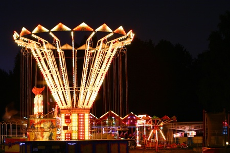 Colorful and glowing amusement park at night time photo