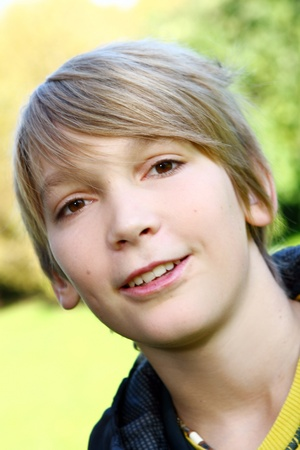 Portrait of young and attractive boy in park photo