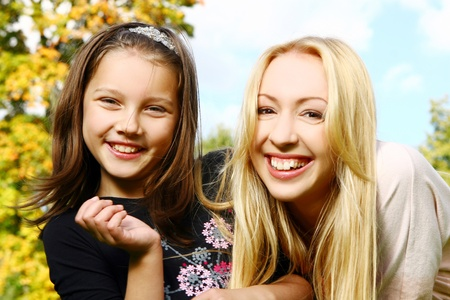 Two smiling sisters have fun in park photo