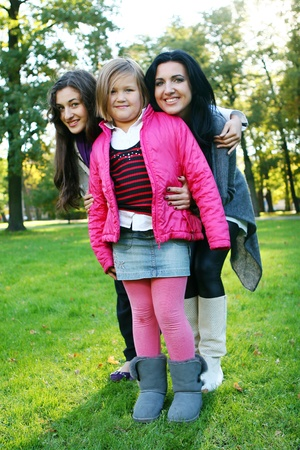Young family taking healthy stroll through autumn park and have fun photo