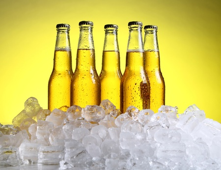 Bottles of cold and fresh beer with ice over yellow background photo