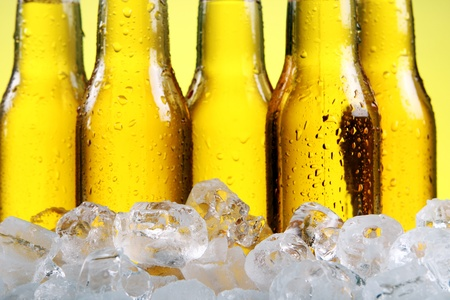 Bottles of cold and fresh beer with ice over yellow background Stock Photo - 9636310