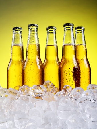 bier glazen: Bottles and Glass of beer with foam over yellow background