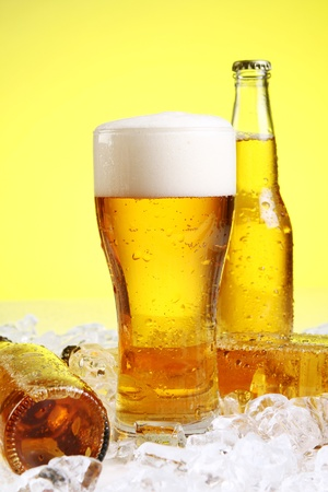 liquid summer: Bottles and Glass of beer with foam over yellow background