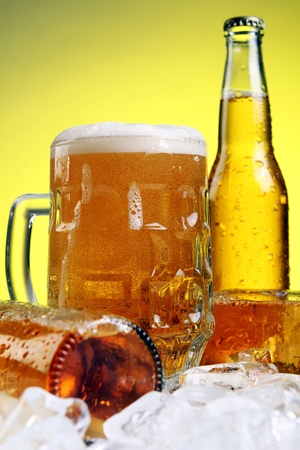 Bottles and Glass of beer with foam over yellow background photo