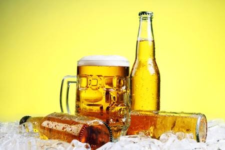 botellas de cerveza: Botellas y vaso de cerveza con espuma sobre fondo amarillo