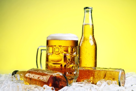 bottle cap: Bottles and Glass of beer with foam over yellow background