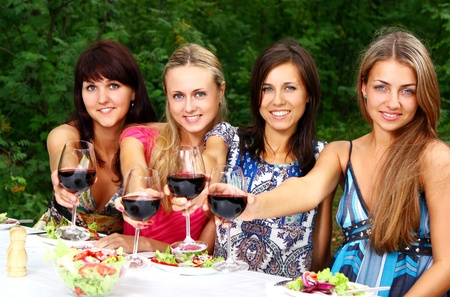 Group of young and beautiful womens drinikg wine in the park photo