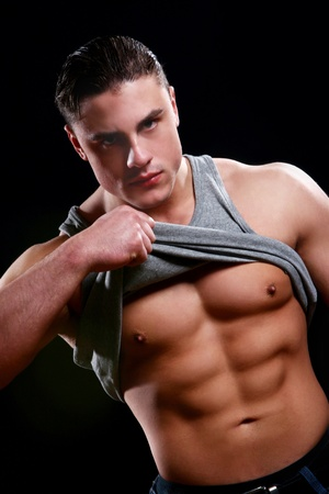 Young bodybuilder shows his body on black background Stock Photo - 9796685