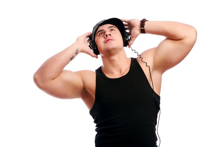 Young muscular man listen music isolated over white background photo