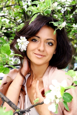 Young and beautiful woman in summer garden photo