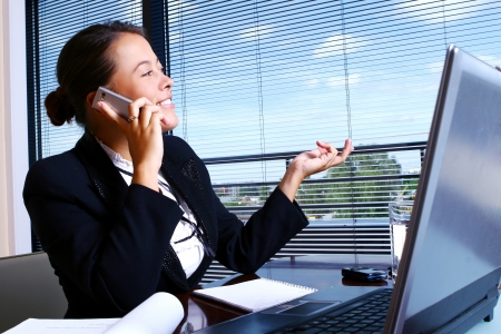 business woman phone: Young businesswoman working in the office