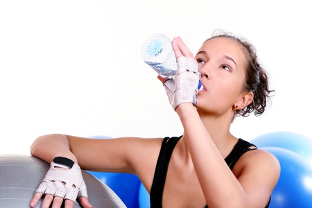 Young and beautiful girl with bottle of mineral water in gym photo