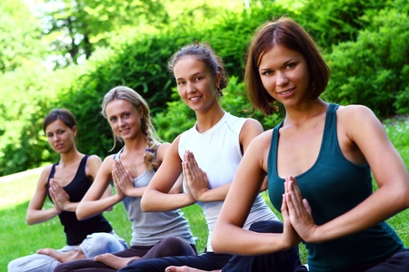 young womens: Grou of young womens doing fitness exercises in park Stock Photo