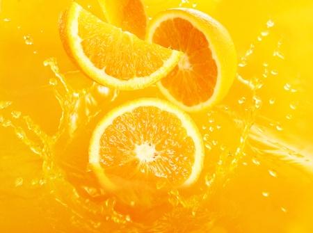 jugo de frutas: Naranjas frescas cayendo en jugo con gran cantidad de enormes salpicaduras Foto de archivo