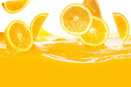 Fresh oranges falling in juice on white background photo