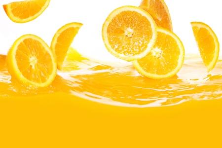 Fresh oranges falling in juice on white background photo