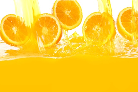 Fresh oranges falling in juice with lot of huge splashes photo