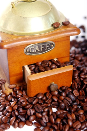 Old coffee grinder and roasted coffee beans over white background photo