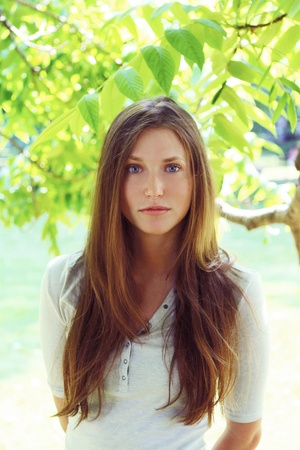 Young and beautiful woman in a tree leaves Stock Photo - 10002074