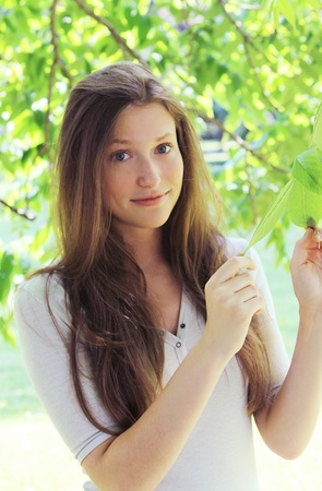 Young and beautiful woman in a tree leaves Stock Photo - 10002067