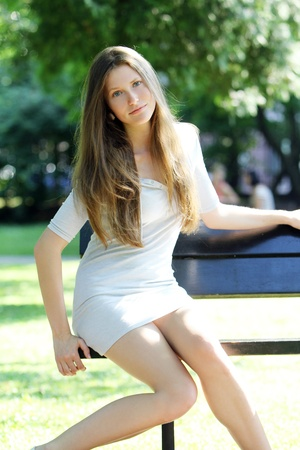 Young and beautiful woman sitting on the bench in park Stock Photo - 10002062