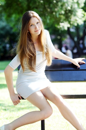 Young and beautiful woman sitting on the bench in park Stock Photo - 10002059