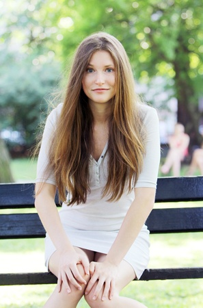 Young and beautiful woman sitting on the bench in park Stock Photo - 10002064