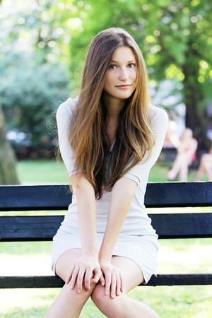 Young and beautiful woman sitting on the bench in park Stock Photo - 10002071