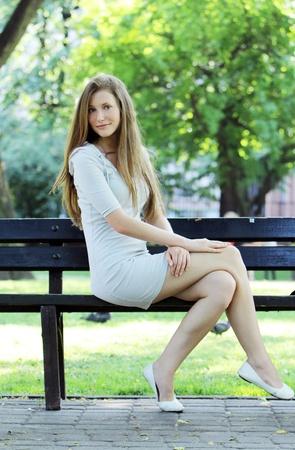 mujer sentada: Joven y hermosa mujer sentada en el Banco en el Parque