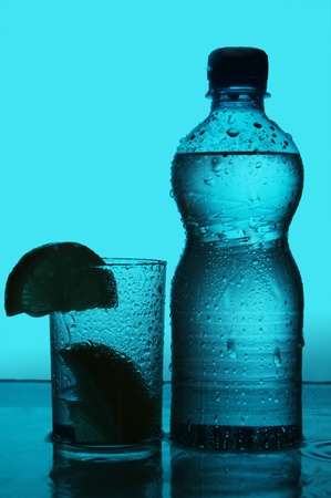 Silhouette of bottle and glass over blue background photo