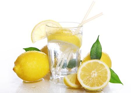 Cocktail with fresh wet lemons on white background Stock Photo