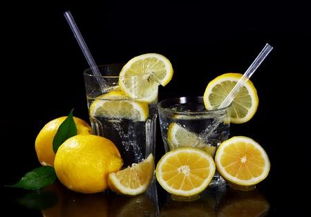 limonada: Cóctel con limón fresco mojado sobre fondo negro Foto de archivo