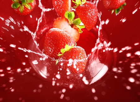 Strawberry falling into the lot of  red juice and makes big splashes Stock Photo