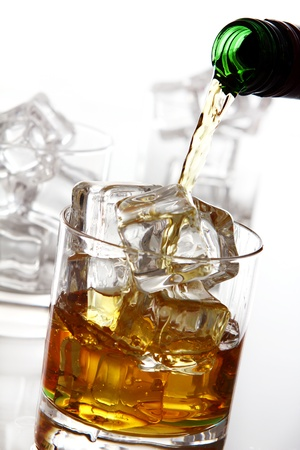 botella de whisky: Whisky fr�o verter en el vaso aislado sobre fondo blanco