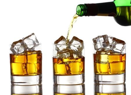 botella de whisky: Whisky frío verter en el vaso aislado sobre fondo blanco