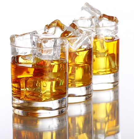 hard liquor: Glasses of cold whiskey with ice isolated over white Stock Photo