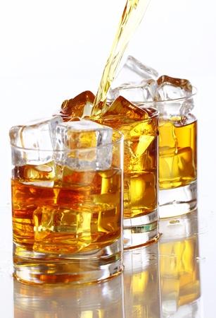 whiskey: Gieten koude whisky in het glas geà ¯ soleerd op witte achtergrond