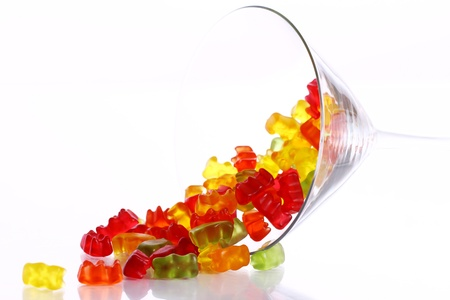 Colorful gummy bear candies  in the glass over white background photo