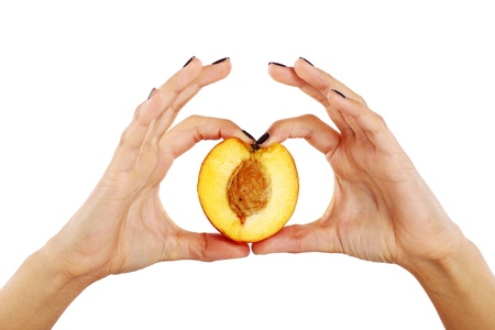 Peach fruit in womans hands isolated over white background photo