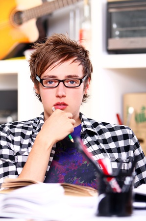Young  student in glasses at home photo