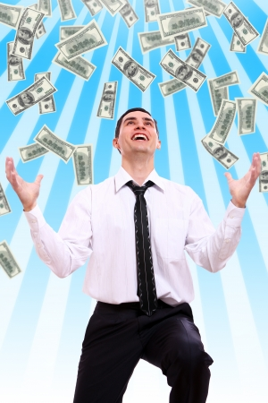 winning stock: Happy businessman and flying dollar banknotes against abstract blue background