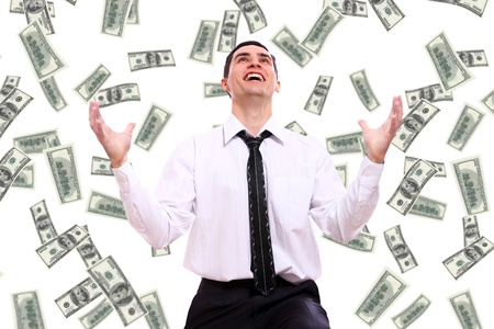 Happy businessman and flying dollar banknotes against white background