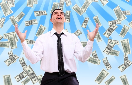 Happy businessman and flying dollar banknotes against abstract blue background photo